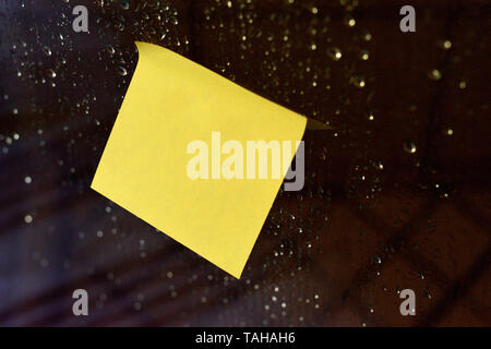 Piece of square sheet use to give notation stick to dewy wet glass window - Stock Photo