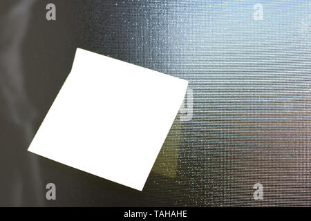 Piece of square paper use to give notation stick to textured glass window - Stock Photo