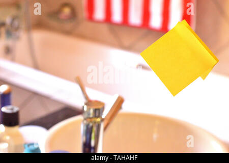 Piece of square yellow sheet use to give notation stick to washroom mirror - Stock Photo