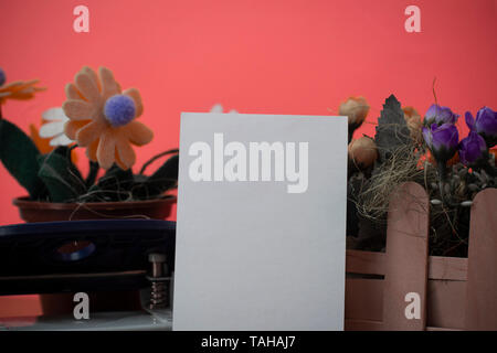 Flowers and writing equipments plus plain sheet above textured backdrop - Stock Photo