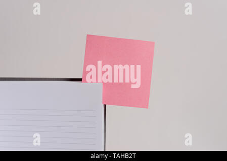Upper view lined hard cover note book sticky note inserted clear background - Stock Photo