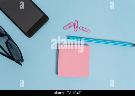 Eyeglasses colored sticky note smartphone cell clips pen pastel background - Stock Photo