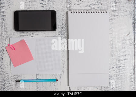 Squared spiral notebook marker smartphone sticky note clip wood background - Stock Photo