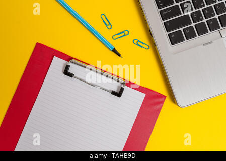Open laptop clipboard blank paper sheet marker clips colored background - Stock Photo