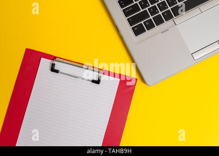 Part view trendy metallic laptop clipboard paper sheet colored background - Stock Photo