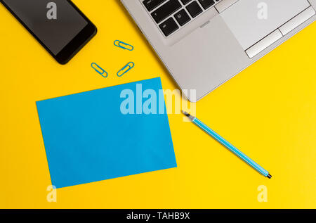 Trendy open laptop smartphone marker paper sheet clips colored background - Stock Photo