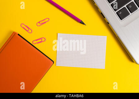 Laptop clips pencil paper sheet hard cover notebook colored background - Stock Photo