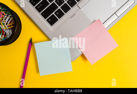 Trendy metallic laptop sticky notes clips container pencil colored background - Stock Photo