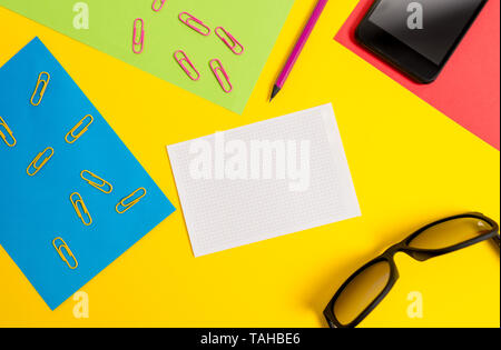 Paper sheets pencil clips smartphone eyeglasses notebook color background - Stock Photo