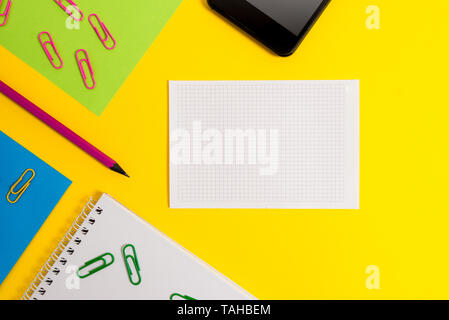 Paper sheets squared notebook pencil clips smartphone colored background - Stock Photo