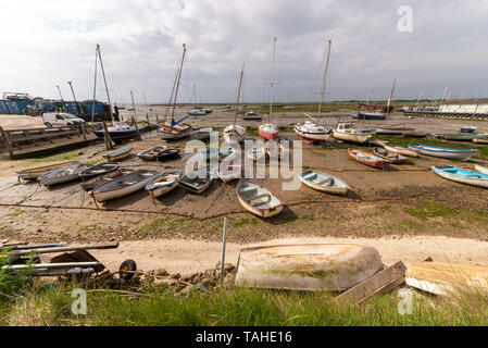 Large numbers of rowing boats and yachts sitting on the mud at Leigh on Sea, Essex, UK at low tide. Changeable weather with threatening cloud - Stock Photo