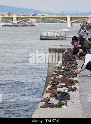 Budapest Shoes on the Danube Bank a memorial by sculptor Gyula Pauer in front of Parliament to the jews shot on the bank in World War II Hungary - Stock Photo