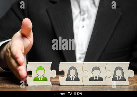 A businessman joins a new employee to the team as its leader. Hiring new employees for the project., teamwork. leader works with the team as a member. - Stock Photo