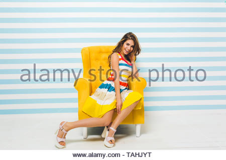 Smiling brunette girl in bright summer dress posing indoors, sitting in big yellow armchair. Portrait of gorgeous young woman with light-brown hair resting in her room on striped background. - Stock Photo