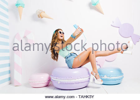Inspired funny girl wearing tank-top and denim shorts sitting on toy macaroon and making selfie. Laughing young lady in sunglasses and headphones taking picture of herself in room with sweet interior - Stock Photo