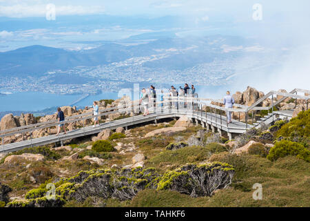 TASMANIA, AUSTRALIA - FEBRUARY 16, 2019: Tourists on a boardwalk on top of Mount Wellington, looking at Hobart, the capital city of Tasmania in Austra - Stock Photo