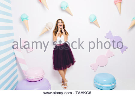 Happy time of joyful young woman in tulle skirt isolated on white background among sweets. Pastel colors, macarons, ice cream, happiness, fashionable model, having fun - Stock Photo