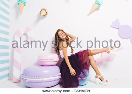 Inspired laughing girl in trendy lush dress chilling on blue macaroon chair with eyes closed. Pretty young lady wearing heeled white shoes relaxing in room decorated with cookie and ice cream. - Stock Photo