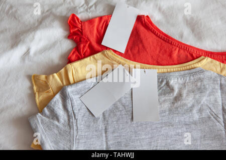 Three new kid's or women's t-shirt, grey, red, yellow colours, with clean label on white background. Concept shopping, summer sales, discounts, organi - Stock Photo