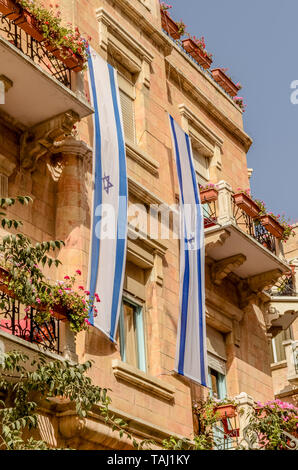 Jewish Star of David flag draping side of building with flowers on balconies on Jaffa Street in Jerusalem, Israel - Stock Photo
