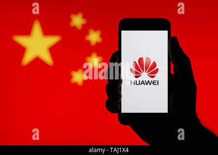 A silhouetted hand of a man holds a smartphone displaying the logo of Chinese company Huawei, with a China flag in the background (Editorial use only) - Stock Photo