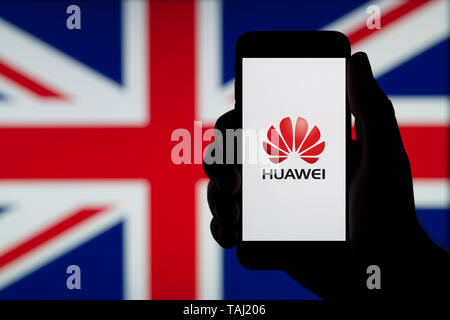 A silhouetted hand of a man holds a smartphone displaying the logo of Chinese company Huawei, with a UK flag in the background (Editorial use only). - Stock Photo