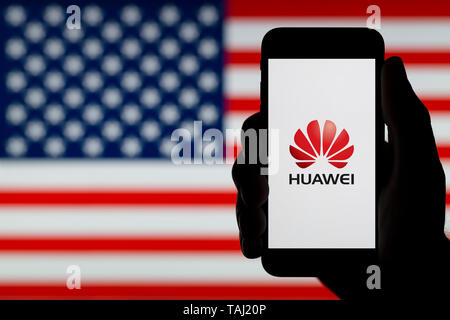 A silhouetted hand of a man holds a smartphone displaying the logo of Chinese company Huawei, with a USA flag in the background (Editorial use only). - Stock Photo