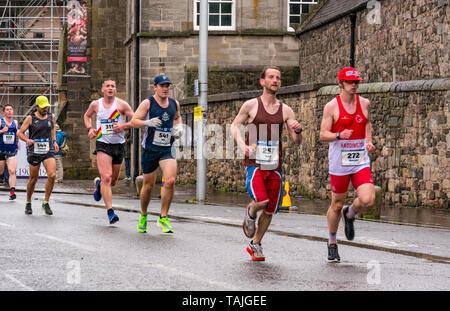 Edinburgh, UK. 26th May 2019. Edinburgh Marathon:  Marathon runners run past Holyrood Palace on a wet windy day. Stamatis Papadakis (544) finished in 40th place; Daniel Brazier (311) finished 27th; Dave Ward (257) finished 22nd - Stock Photo