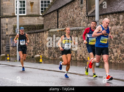 Holyrood, Edinburgh, Scotland, United Kingdom, 26 May 2019. Edinburgh Marathon: Lead marathon runners run past Holyrood Palace on a wet and windy day. John Prichard-Taylor (485) finished in 18th place; Melanie Wilkins (490) first female runner over finishing line and in 24th place overall; Brendan O'Grady (82428) finished 33rd; Tom Fairbrother (82482) finished 13th - Stock Photo