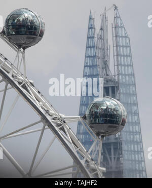 London, UK. 26th May 2019. Distant view of tourists on a London Eye pod against a background with top of The Shard shimmering through heat haze. Distance from imaging position to The Shard was 2.39 miles or 3.84 km. Credit: Malcolm Park/Alamy Live News - Stock Photo