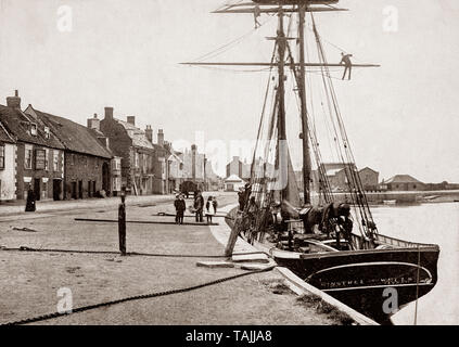 A late 19th Century view of 'Minstrel', a sailing ship in the harbour of Wells-next-the-Sea, aka Wells, a port on the North Norfolk coast of England. The town started to be known as Wells-next-the-Sea in the early 19th century to distinguish it from other places of the same name. When the Wells and Fakenham Railway was opened on 1 December 1857, the terminus was given the name of 'Wells-on-Sea'. In 1956 the Wells Urban District Council voted to (re-)adopt the name Wells-next-the-Sea, and this has been the official name since then. - Stock Photo