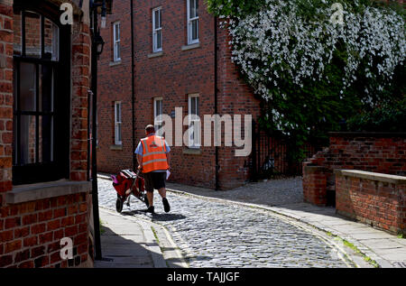 Postman delivering mail on cobbled street in Howden, East Yorkshire, England UK - Stock Photo