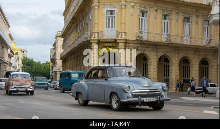 Havana, Cuba - A taxi passes in front of Hotel Plaza near Parque Central. Classic American cars from the 1950s, imported before the U.S. embargo, are  - Stock Photo