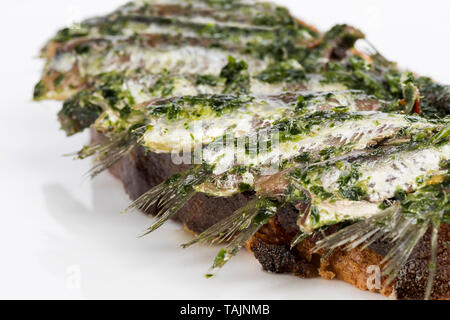 anchovies on bread oil and parsley - Stock Photo