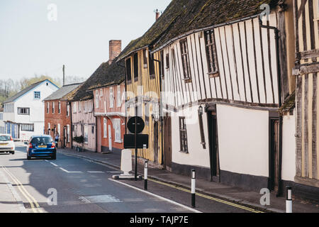 Lavenham, UK - April 19, 2019: Car driving past half-timbered medieval cottages in Lavenham, a village in Suffolk, England, famous for its Guildhall,  - Stock Photo