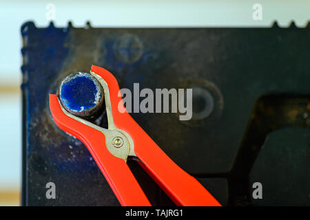 Close-up veiw of charging an old car battery, red clamp on positive side - Stock Photo
