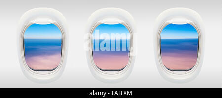 Windows of airplane from inside, blue sky and pink clouds, aerial travel concept - Stock Photo