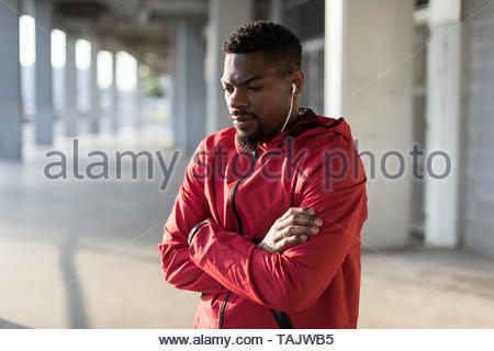 Portrait of motivated sportsman listening music during urban outdoor workout. - Stock Photo