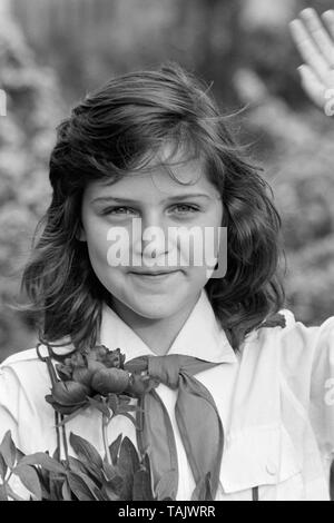 young schoolgirl member of the pioneer movement wearing her necktie and uniform while holding a bunch of flowers and saluting 1970s hungary - Stock Photo
