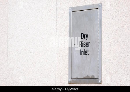 Dry riser steel silver box architrave on building wall - Stock Photo