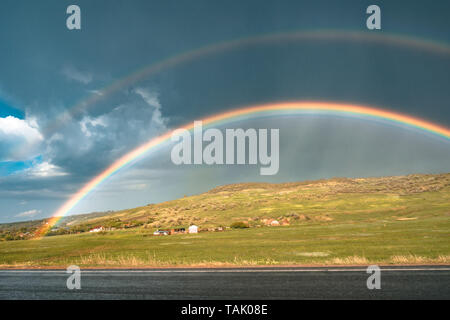 Rainbow on the road with clouds on sky, dark sky, rainy outside. Rainbow and storm at the same time - Stock Photo
