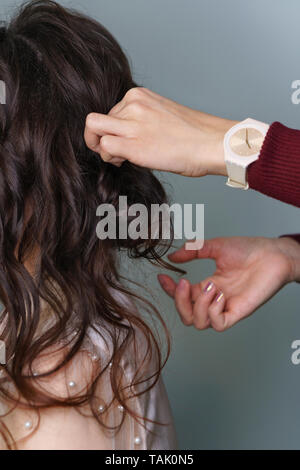 Preparation of bride. Hairstylist at work in process of creating hairstyles. Brown-haired person girl, side-view long hair, hairstyle collected, styli - Stock Photo