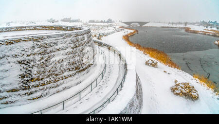 Spiralling path going up a bridge near an icy lake in Daybreak Utah. Footprints are imprinted on the powdery white snow covering the shoreline and pat - Stock Photo