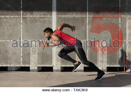 Young black urban athlete running and sprinting. - Stock Photo