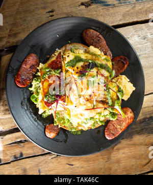 Breakfast egg omelette with sausage, spinach and bread on plate set on wooden table - Stock Photo