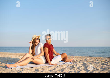 Young diverse race couple sitting back to back on beach towel at tropical travel location. Lovers at beautiful sea view on honeymoon or dating. Man - Stock Photo