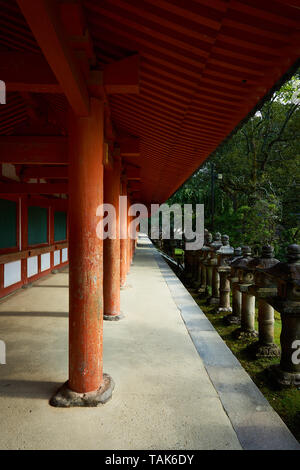 Vermillion columns and old stone lanterns line the veranda around the outside of Kasuga Taisha Grand Shrine in Nara, Japan. - Stock Photo