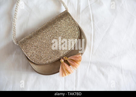 Small golden saddle handbag with tassels and rope handle lies on rumpled white sheet. Concept fees, outfitting, kid's fashion, basic wardrobe. Copy sp - Stock Photo