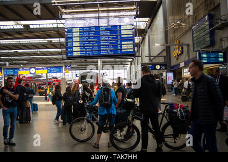 Munich,Germany- May 25,2019:Passengers ok at a sign showing the next trains leaving in the departures hall at Munich Central Station - Stock Photo