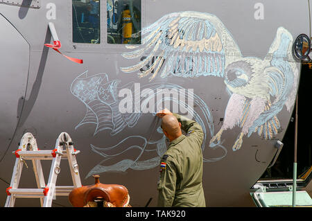Air Force crewman chalking an eagle picture on the nose of a Lockheed C-130 Hercules transport plane. US Air Force military nose art. RIAT Cotswolds - Stock Photo